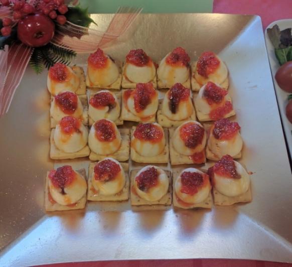 Bombón de queso curado con anchoas y cobertura de confitura de pimiento rojo